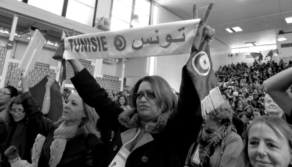 A Tunisian woman holds up peace signs at the Women's Assembly at the 2013 World Social Forum