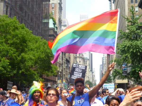 A young Black person in an AVP tee shirt with a high top fade waves the Pride flag. Image courtesy Robin J. Hayes