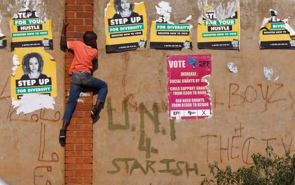A child climbs past defaced election posters during an election rally of President Jacob Zuma's African National Congress (ANC) in Bekkersdal township south of Johannesburg. Image courtesy of the Baltimore Sun.