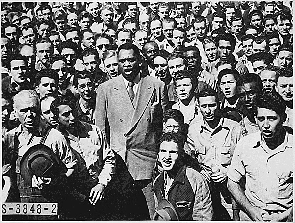 Paul Robeson among a crowd of racially integrated shipyard workers in Oakland, California,  performing the Star Spangled Banner.