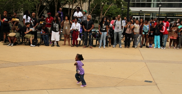 A child runs through a large circle of attendees performing a ritual of healing and solidarity.